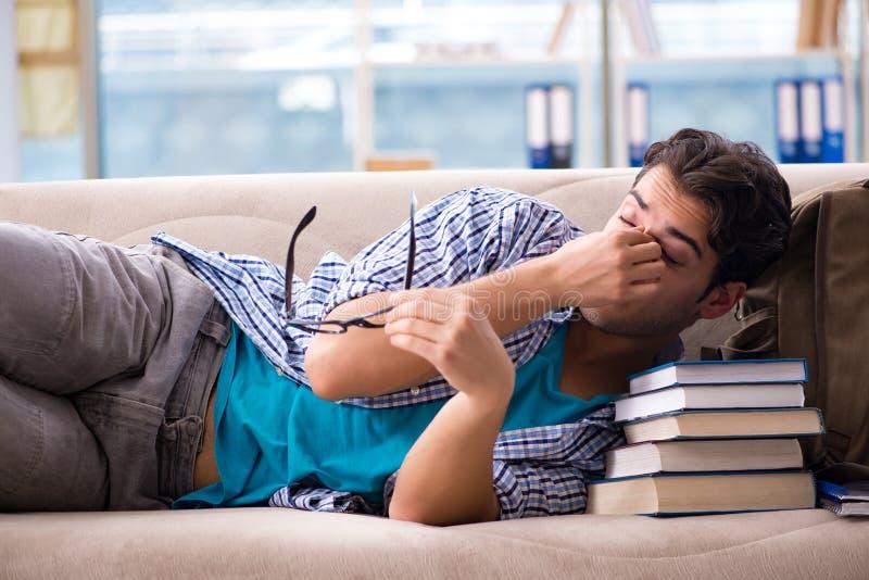 Утомленный студент лежа на софе стоковая фотография