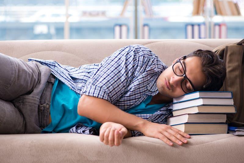 Утомленный студент лежа на софе стоковое изображение rf