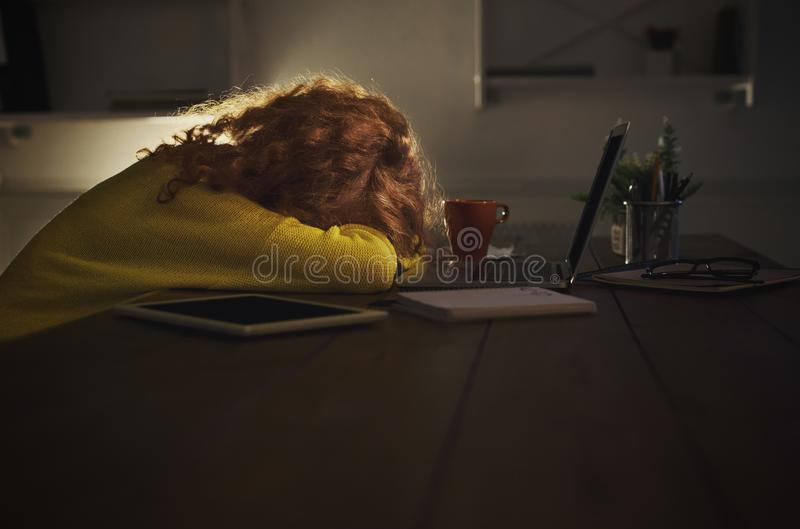 Утомленный фрилансер работая на компьтер-книжке дома до последнего вечера стоковые изображения rf