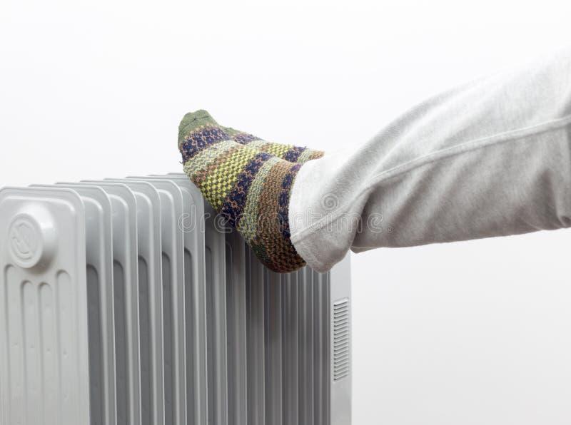 Утомленный человек принимая остатки и получая теплый на подогревателе концепция 2018 зимних отдыхов дома художническая детальная  стоковое изображение