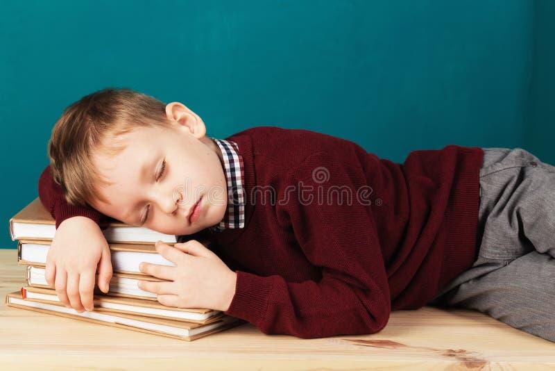 Утомленный школьник уснувший на книгах маленький студент спать на tex стоковая фотография rf