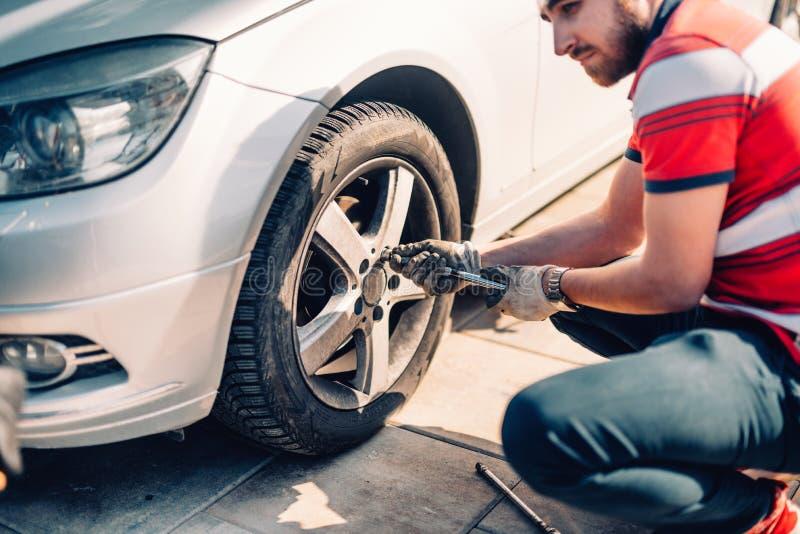 Утомляйте обслуживание, поврежденную покрышку автомобиля или изменяя сезонные автошины используя ключ Изменяющ автошину плоского  стоковая фотография rf