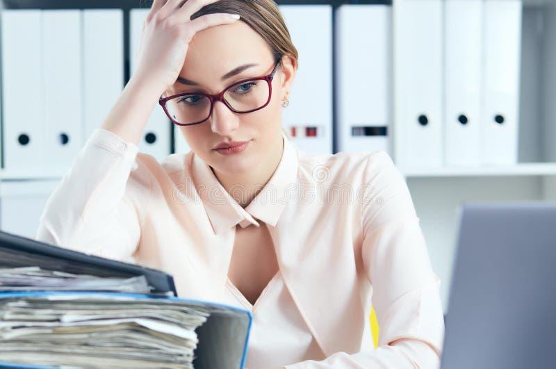 Утомлянная и вымотанная женщина в зрелищах смотрит гору документов подпирая вверх ее голову с ее руками стоковое изображение rf