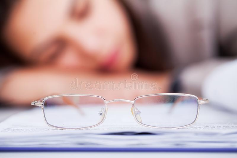 Утомлянная и перегружанная бизнес-леди спать на работе стоковое изображение