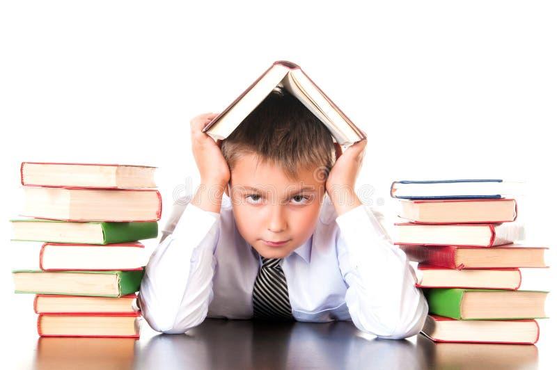Утомлянный, запозданный мальчик школьника сидит в библиотеке с книгами и учит уроки Нехотение выучить стоковое изображение rf