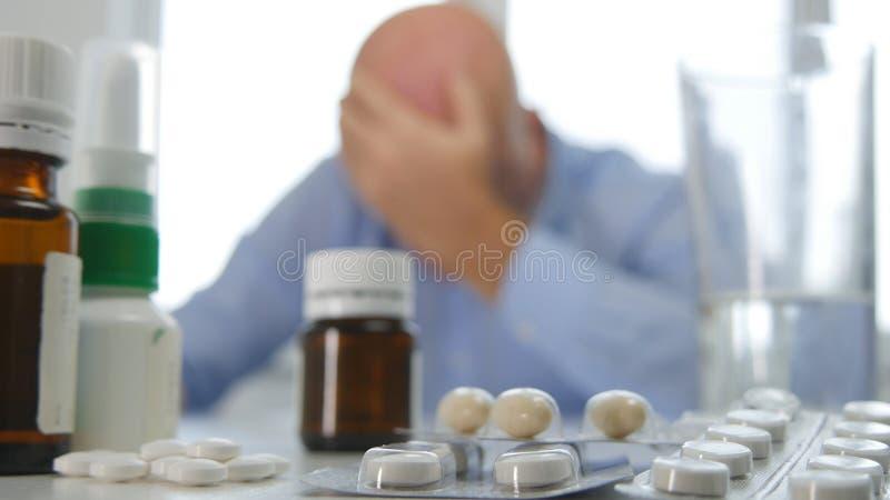 Утомлянный и больной с медицинскими таблетками на таблице держа его голову с рукой стоковое изображение rf