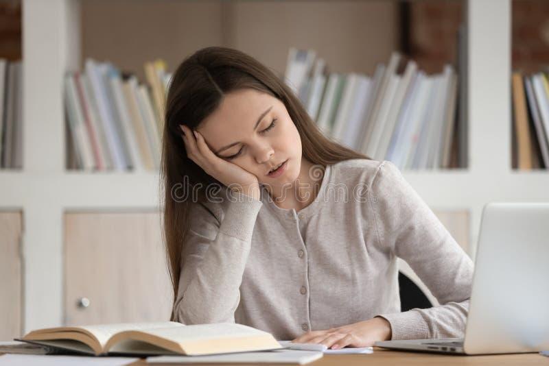 Утомлянный студент девушки падает уснувший изучать на рабочее место стоковые изображения