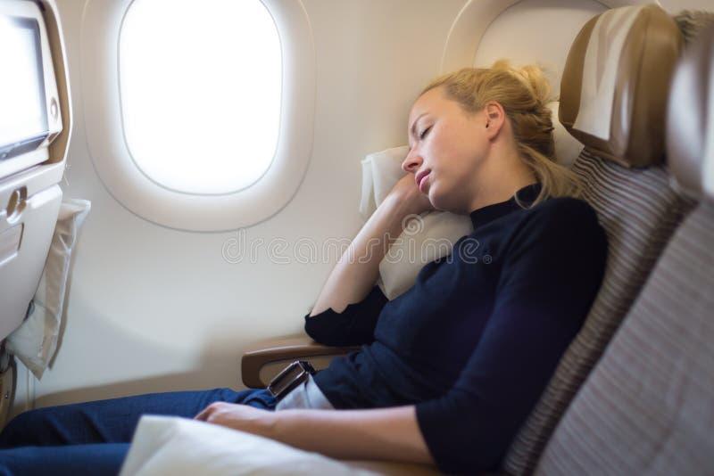 Утомленная белокурая вскользь кавказская женщина napping на самолете стоковое изображение