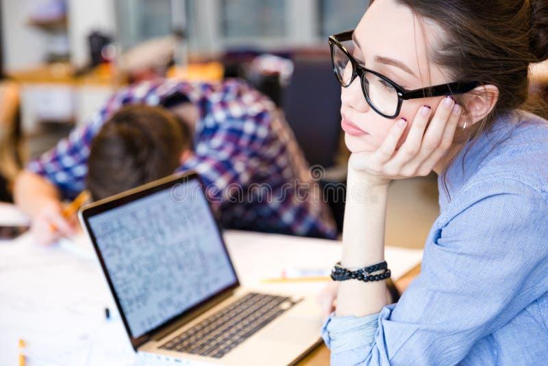 Утомленная женщина при компьтер-книжка сидя в конференц-зале стоковые изображения rf