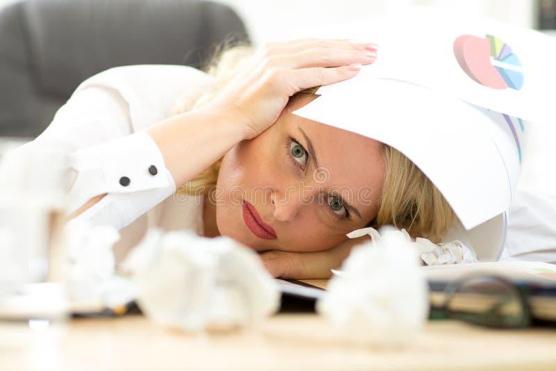 Утомленная исполнительная власть женщины заполняя вне документы пока сидящ на ее столе стоковое фото