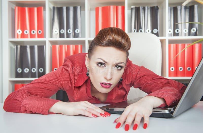 Утомленная коммерсантка работая в офисе Концепция перегрузок стоковая фотография