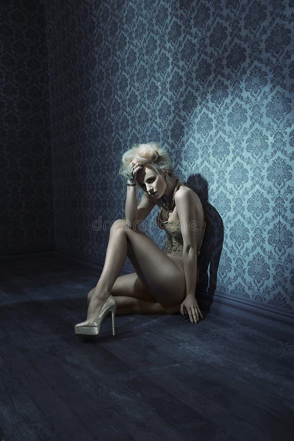 Утомленная молодая дама сидя на поле grunge в темной комнате стоковые изображения rf