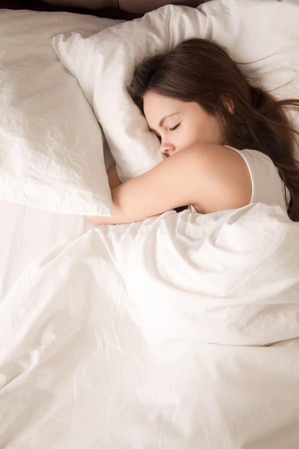 Утомленная молодая женщина спит хорошо в кровати стоковые изображения