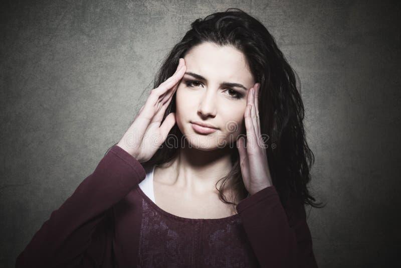 Утомленная молодая женщина с головной болью стоковые фотографии rf