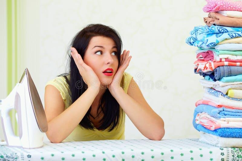 Утомленная домохозяйка с огромной кучей проутюживенной прачечного стоковые фото