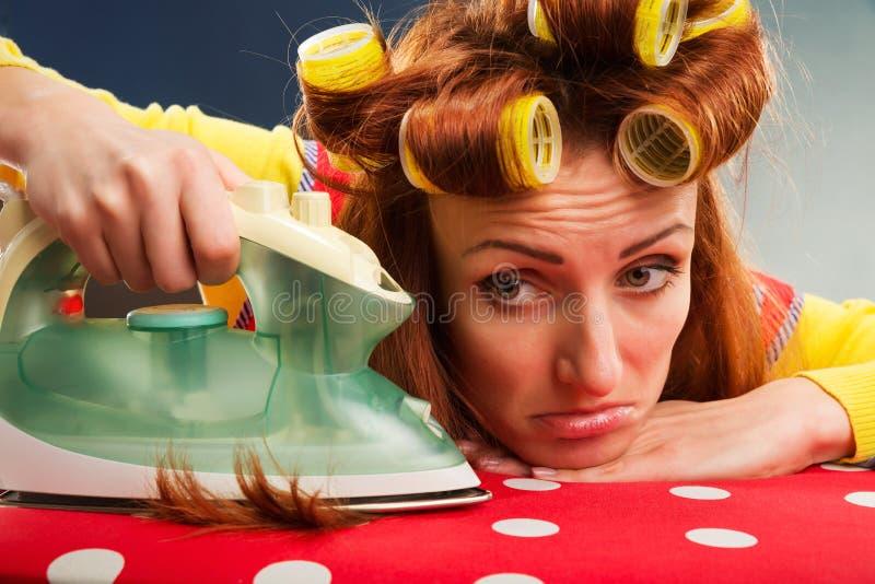 Утомленная домохозяйка с утюжить-доской стоковые фото