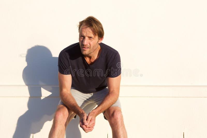 Утомленная склонность человека спорт против белой стены стоковое изображение rf