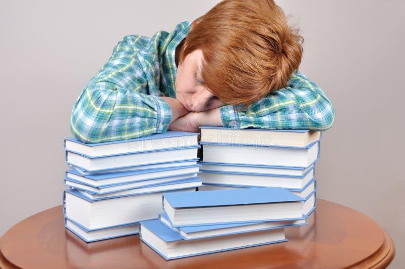 Утомленные женщина и книги стоковые изображения