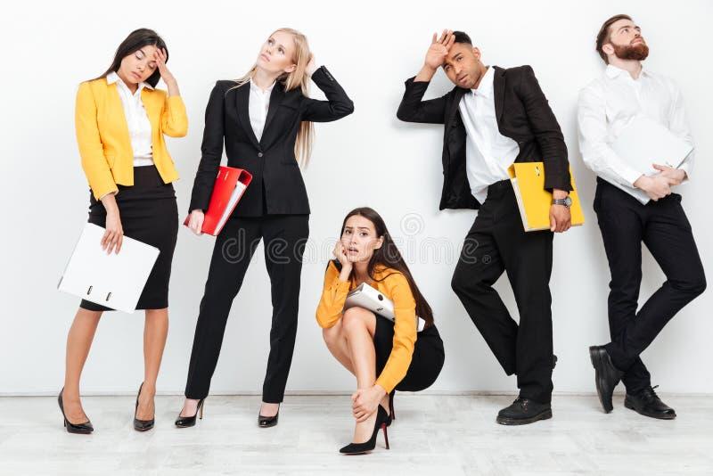 Утомленные коллеги стоя изолированный с папками в офисе стоковая фотография
