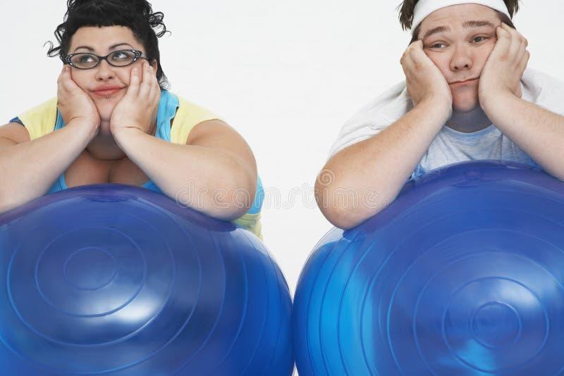 Утомленные полные пары отдыхая на шариках тренировки стоковые фотографии rf
