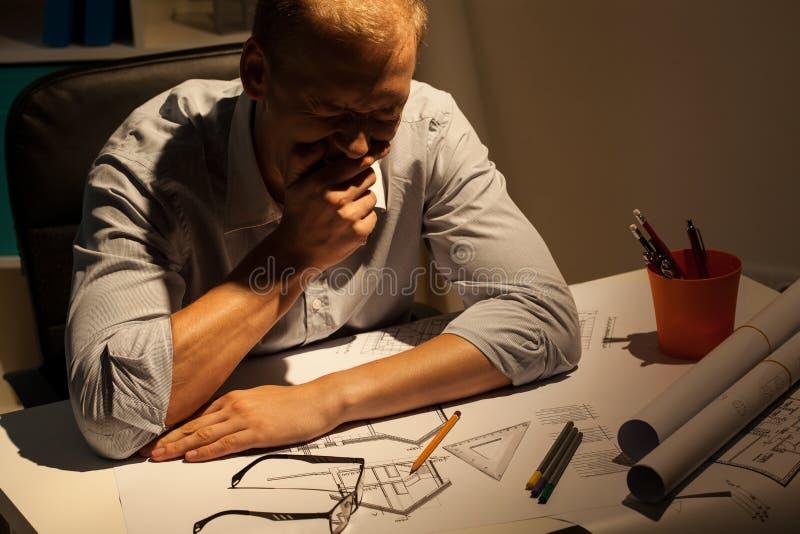 Утомленный архитектор на работе стоковая фотография