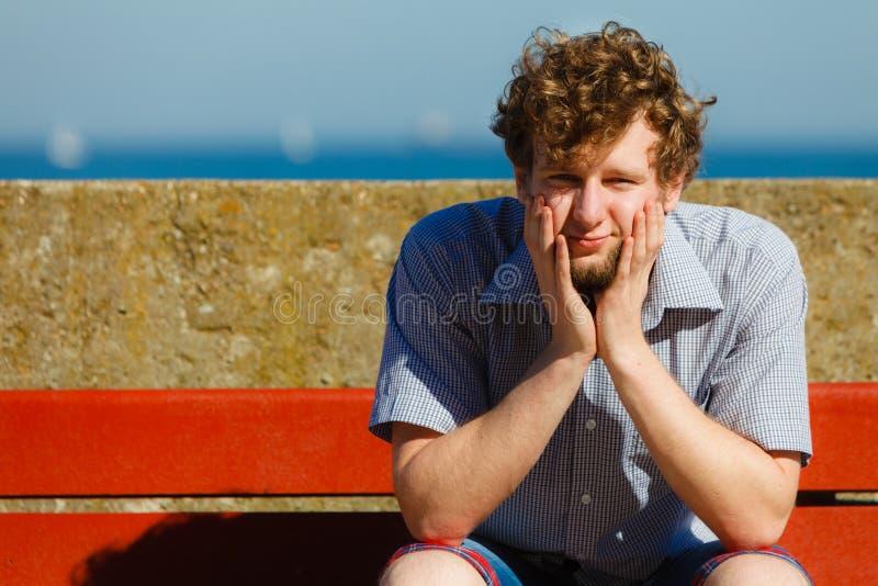 Утомленный вымотанный человек сидя на океане стенда морским путем стоковое изображение