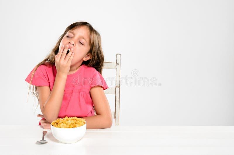 Утомленный маленький ребенок с шаром хлопий для завтрака стоковое фото rf