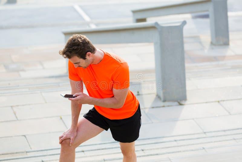Утомленный мужской бегун используя телефон клетки пока отдыхающ после jog снаружи в летнем дне стоковые фотографии rf
