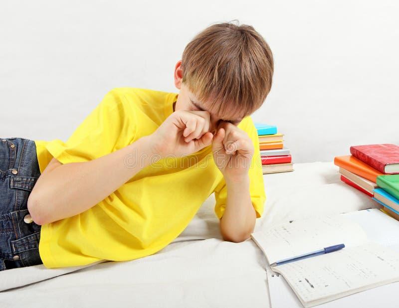 Утомленный подросток делая домашнюю работу стоковые фото