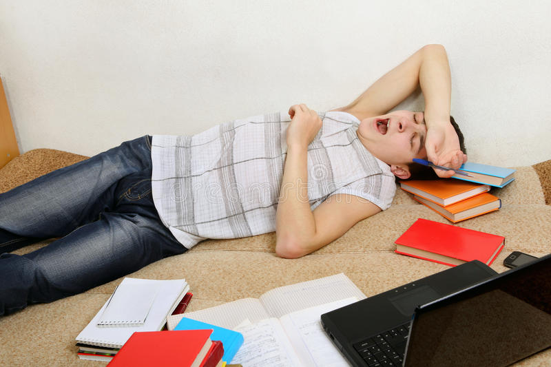 Утомленный подросток зевая на софе стоковые изображения rf
