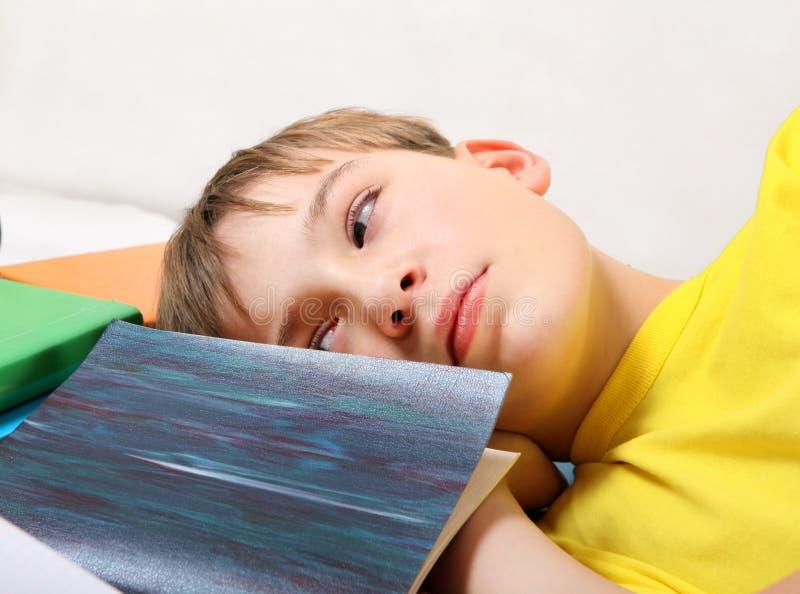 Утомленный подросток с книгами стоковая фотография