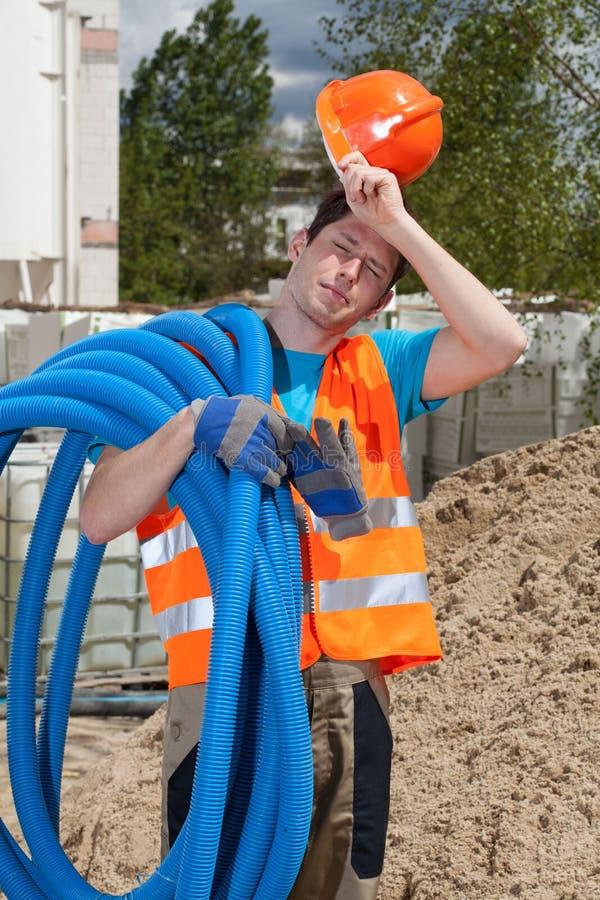 Утомленный рабочий-строитель держа трубы стоковые фото