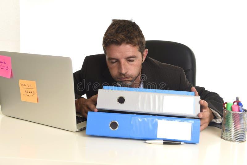 Утомленный расточительствованный бизнесмен работая в стрессе на портативном компьютере офиса вымотался сокрушанный стоковая фотография