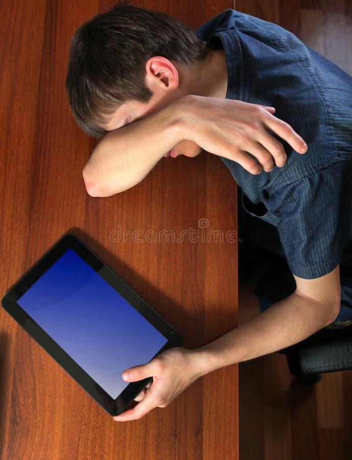 Утомленный сон человека с таблеткой стоковые изображения rf