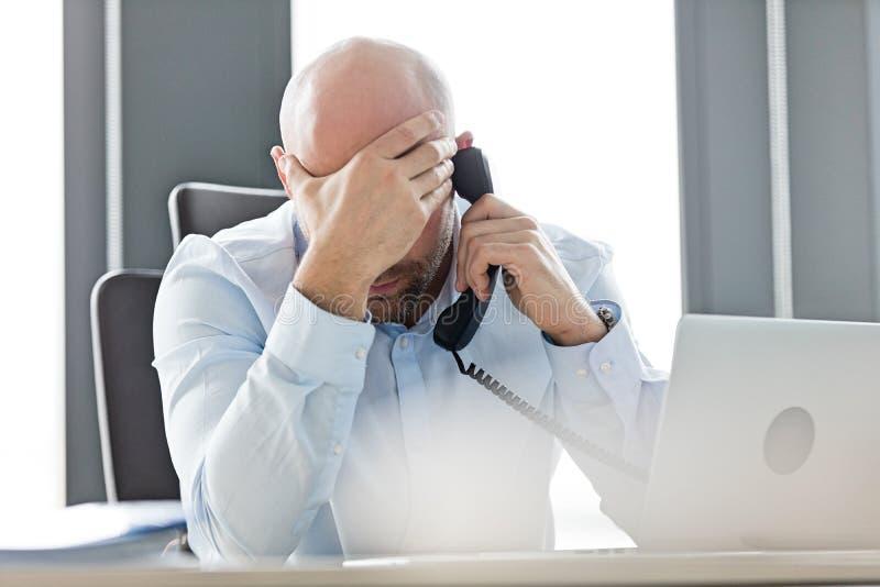 Утомленный средний взрослый бизнесмен используя телефон назеиной линии на столе в офисе стоковое изображение rf