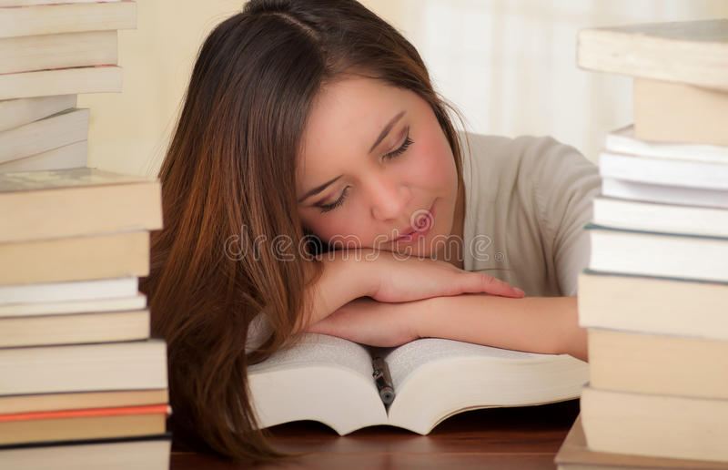 Утомленный студента сон совершенно над книгами в библиотеке стоковая фотография