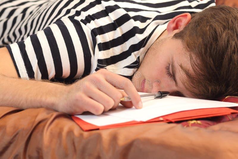 Утомленный студент отдыхая в его спальне стоковая фотография