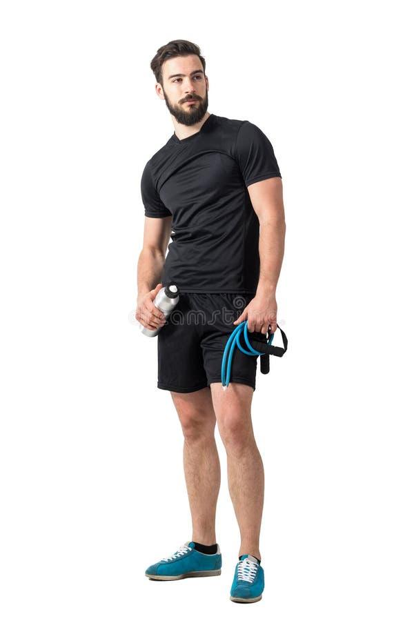 Утомленный тренер фитнеса при диапазоны сопротивления и пластичная бутылка смотря прочь стоковые фото
