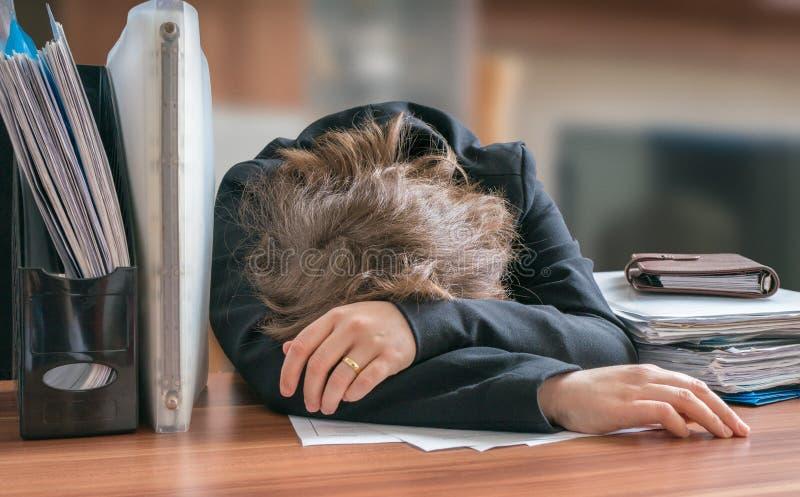 Утомлянная и вымотанная женщина трудоголика спать на столе в офисе стоковые фото