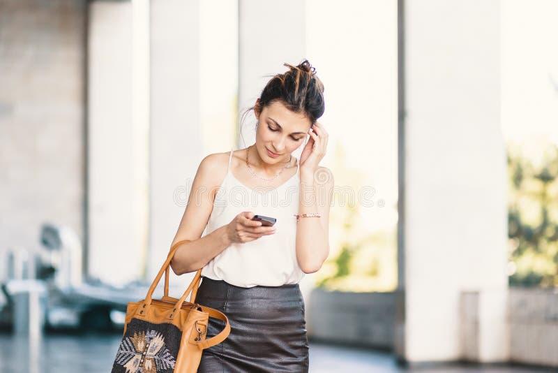 Уточненная усмехаясь женщина идя и писать или читая сообщение SMS стоковые фотографии rf