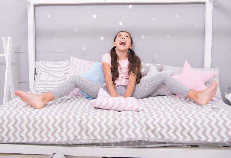 Утро дня рождения Девушка ребенок сидит на кровати счастливой смотрит вверх Ребенк бодрствующий и полный энергии Приятное время о стоковая фотография rf