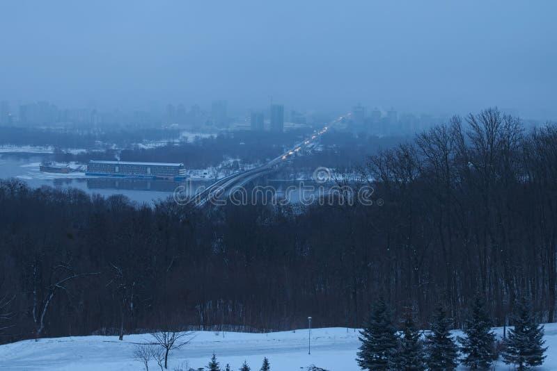 Утро зимы в Kyiv Взгляд к городу на левобережном реке Dnipro Дома прячут в тумане стоковое изображение