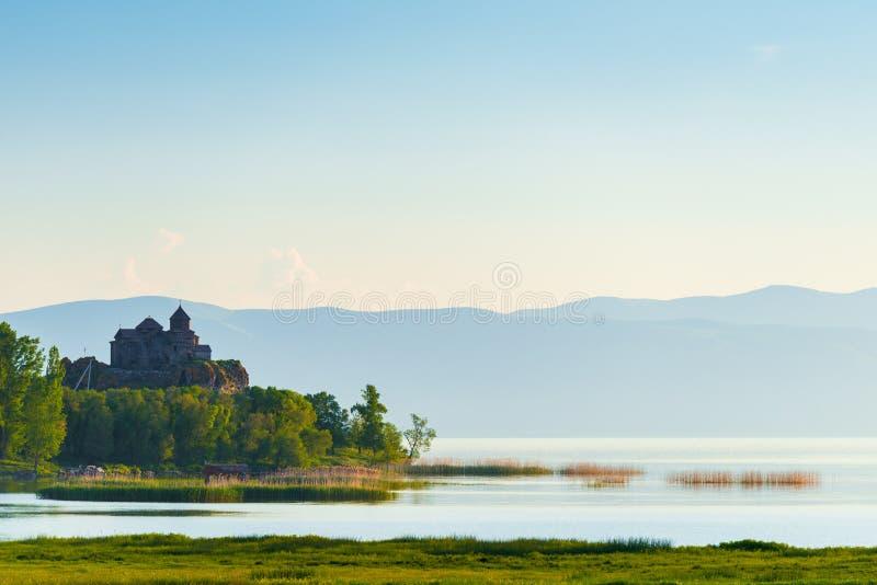 Утро на озере Sevan, взгляде монастыря на озере в лучах восходящего солнца стоковое изображение
