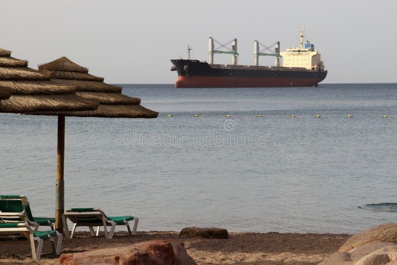 Утро на пляже публики Eilat Большой грузовой корабль на горизонте стоковые фотографии rf