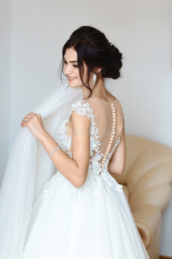 Утро ` s невесты Свадьба изящного искусства Портрет молодой красивой нежной невесты в белом платье свадьбы шнурка грациозно полож стоковые фотографии rf