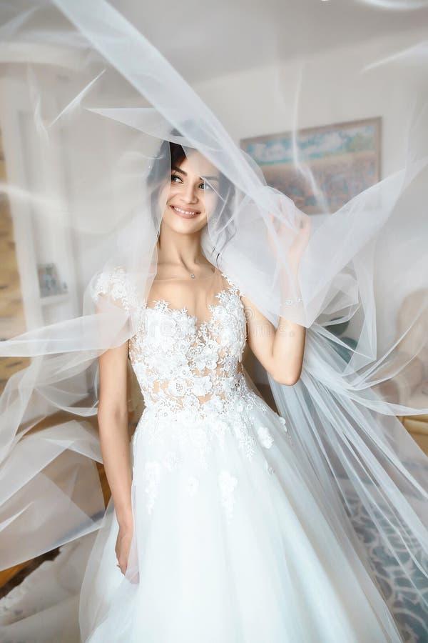 Утро ` s невесты Свадьба изящного искусства Портрет молодой красивой нежной невесты в белом платье свадьбы шнурка грациозно полож стоковые фото