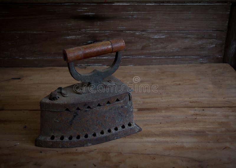 Утюг антиквариата, старый утюг, старый утюг угля на старом деревянном поле ST стоковые изображения