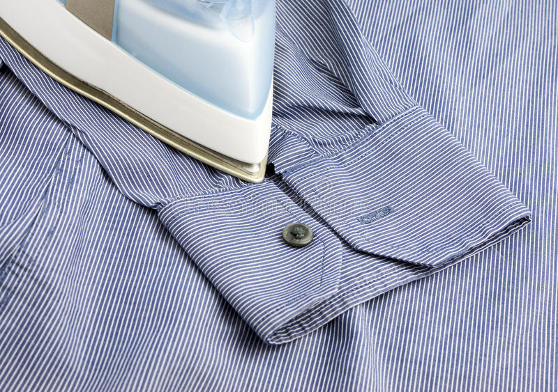 Утюг пара на голубой рубашке стоковые фото