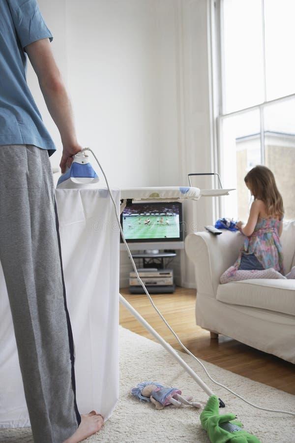 Утюжить и дочь человека на софе телевидением стоковая фотография