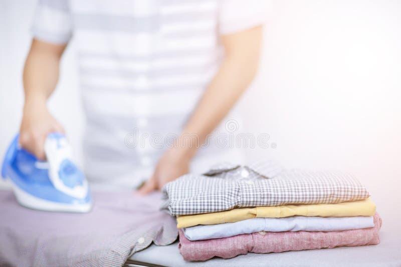 Утюжить человека дома электрические и разнообразие одежд кучи цветов Люди утюжа рубашку на утюжа доске с испаряться голубой утюг стоковое фото